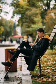 공원에서 벤치에 앉아 음악을 듣고 젊은 남자