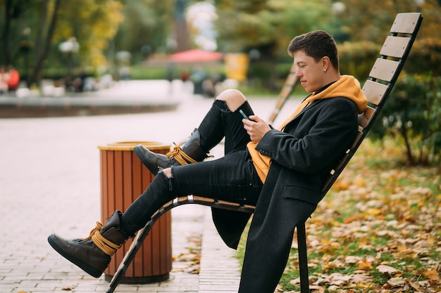 Молодой человек сидит на скамейке в парке и слушает музыку