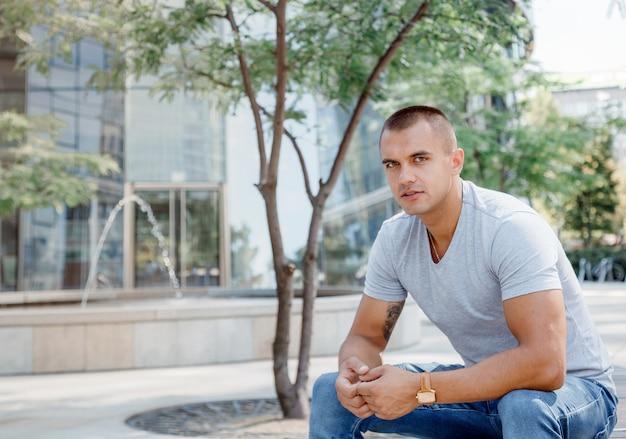 Молодой человек сидит на скамейке. парень в прозрачной футболке и синих штанах. парень на европейской площади в варшаве. польша.
