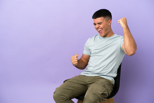 Молодой человек, сидящий на стуле на изолированном фоне, празднует победу