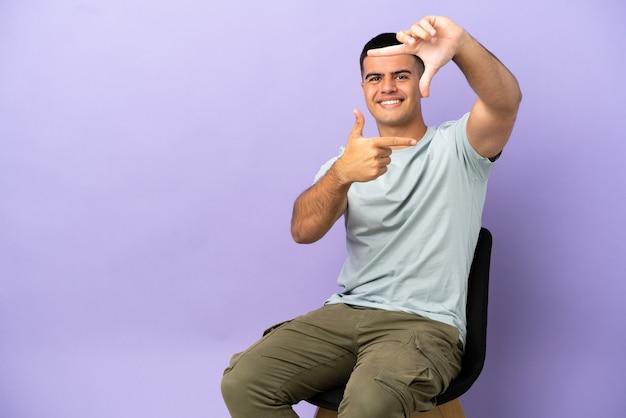 고립 된 배경 초점 얼굴 위에 의자에 앉아 젊은 남자. 프레임 기호