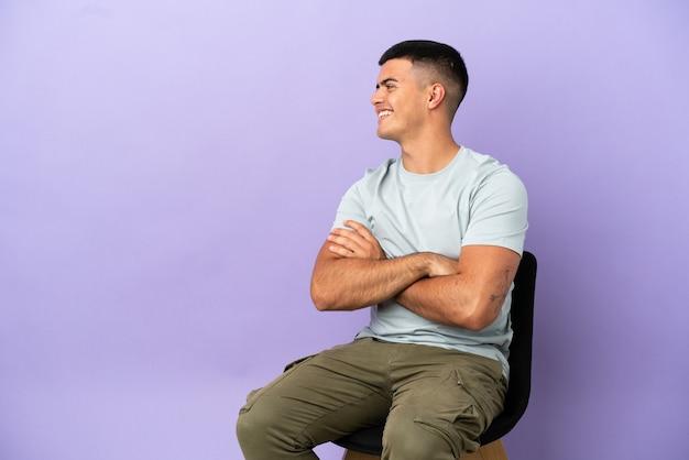 측면 위치에 고립 된 배경 위에 의자에 앉아 젊은 남자