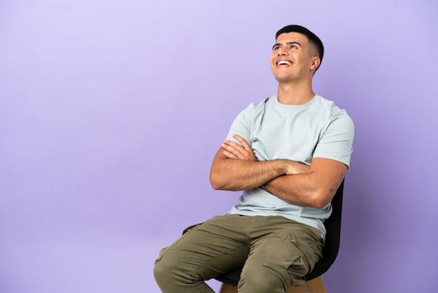 笑顔で見上げる孤立した背景の上に椅子に座っている若い男