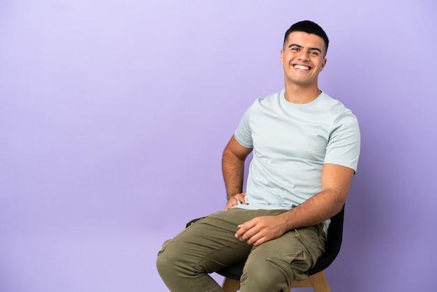 Молодой человек сидит на стуле на изолированном фоне, позирует с руками на бедрах и улыбается
