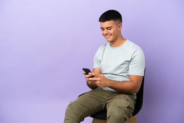 외진 배경 위에 의자에 앉아 모바일로 메시지를 보내는 젊은 남자