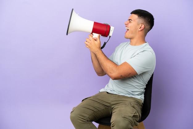 Молодой человек сидит на стуле на изолированном фоне и кричит в мегафон