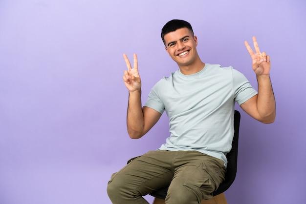 両手で勝利のサインを示す孤立した背景の上の椅子に座っている若い男