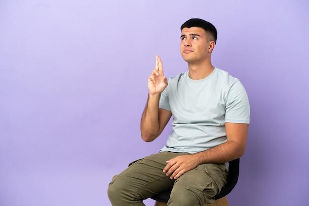 Молодой человек сидит на стуле на изолированном фоне со скрещенными пальцами и желает лучшего
