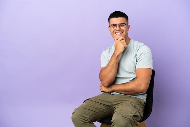 Молодой человек сидит на стуле на изолированном фоне в очках и улыбается Premium Фотографии