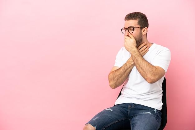 Молодой человек сидит на стуле на изолированном розовом фоне и много кашляет