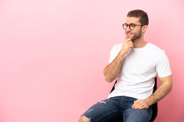 横を見て笑っている孤立したピンクの背景の上の椅子に座っている若い男
