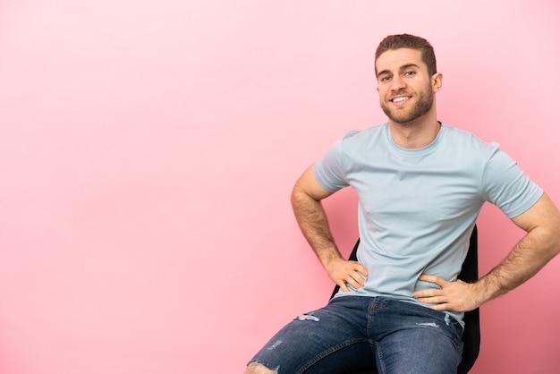 격리 된 분홍색 배경 위에 의자에 앉아 젊은 남자 엉덩이에 팔을 포즈와 미소
