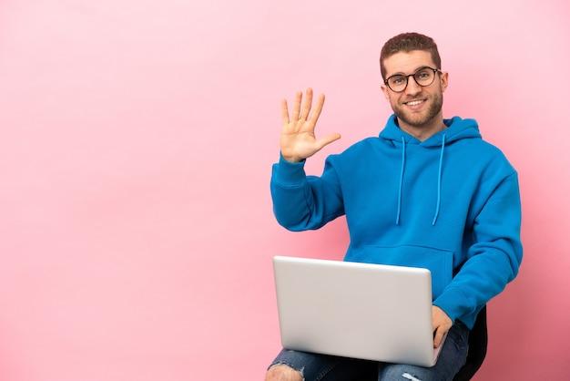손가락으로 다섯을 세는 노트북으로 의자에 앉아 있는 청년