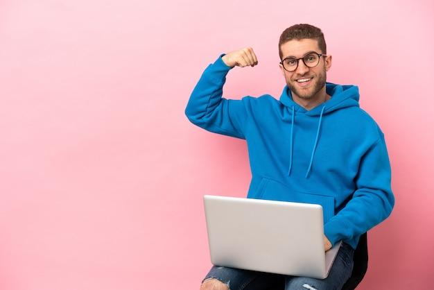강한 제스처를 하 고 노트북으로 의자에 앉아 젊은 남자