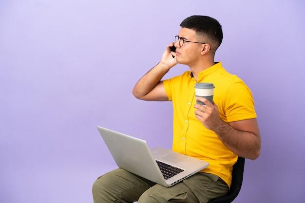 Молодой человек сидит на стуле с ноутбуком, держа кофе на вынос и мобильный