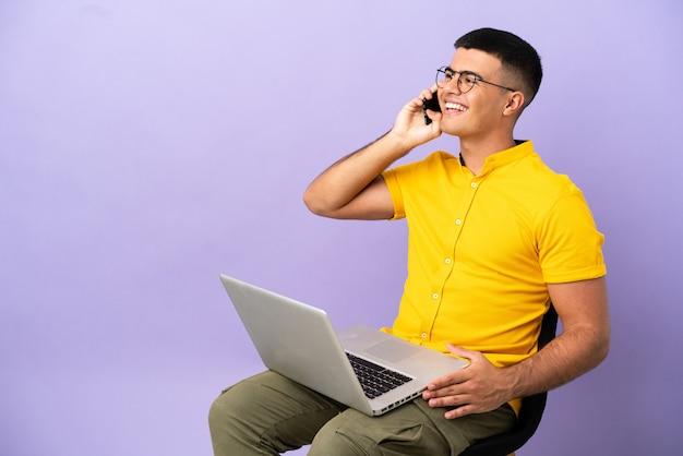 Молодой человек сидит на стуле с ноутбуком, разговаривает по мобильному телефону