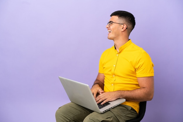 Молодой человек сидит на стуле с ноутбуком, смеясь в боковом положении