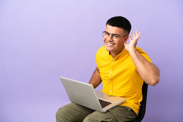 Молодой человек сидит на стуле с ноутбуком, слушая что-то, положив руку на ухо