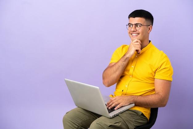 Молодой человек сидит на стуле с ноутбуком, глядя в сторону