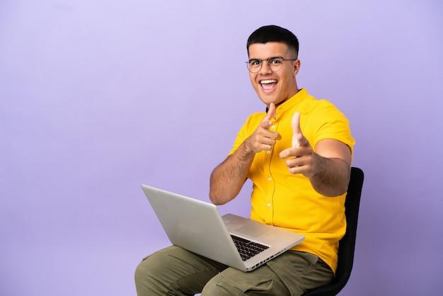 Молодой человек сидит на стуле с ноутбуком, указывая вперед и улыбается