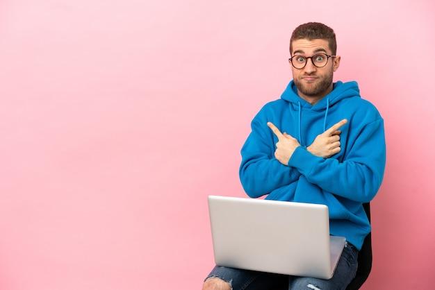 Молодой человек сидит на стуле с ноутбуком, указывая на боковые стороны, сомневаясь