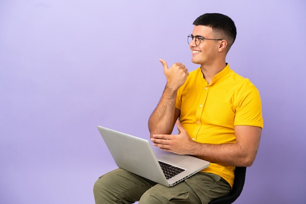 Молодой человек сидит на стуле с ноутбуком, указывая в сторону, чтобы представить продукт