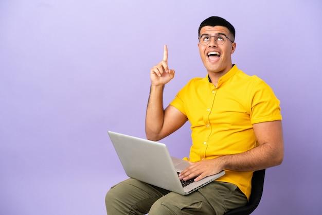 Молодой человек сидит на стуле с ноутбуком, указывая вверх и удивлен