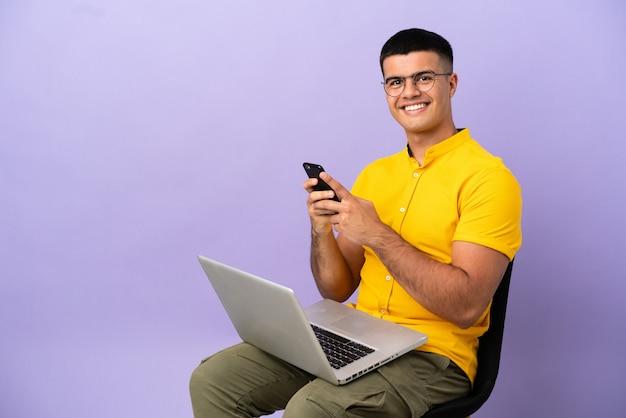 Молодой человек сидит на стуле с ноутбуком, отправляя сообщение с мобильного телефона