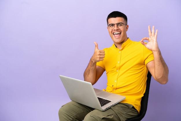 Молодой человек сидит на стуле с ноутбуком, показывая знак ок и жест пальца вверх