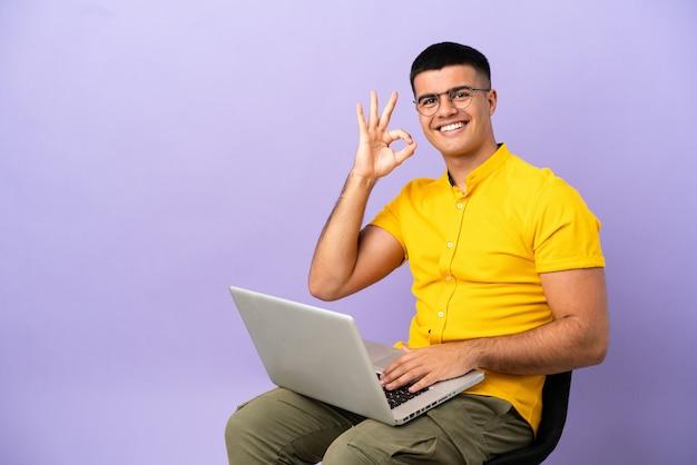 Молодой человек сидит на стуле с ноутбуком, показывая пальцами знак ок