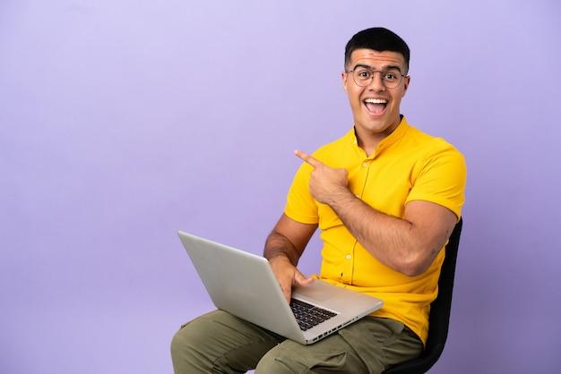 Молодой человек, сидящий на стуле с ноутбуком, удивлен и указывает сторону