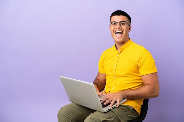 Молодой человек сидит на стуле с ноутбуком с удивленным выражением лица