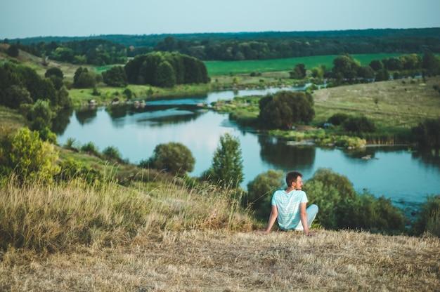若い男が芝生の上の丘の上に座って、雄大な自然の風景を楽しみ、景色を楽しみます。勝者の成功のコンセプト。