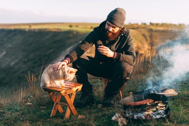 彼の手にコーヒーを持ってグリルの近くに彼の猫と一緒に丘の上に座っている若い男