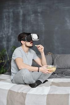 バーチャルリアリティゴーグルで映画を見ながらベッドに座ってチップを食べる若い男