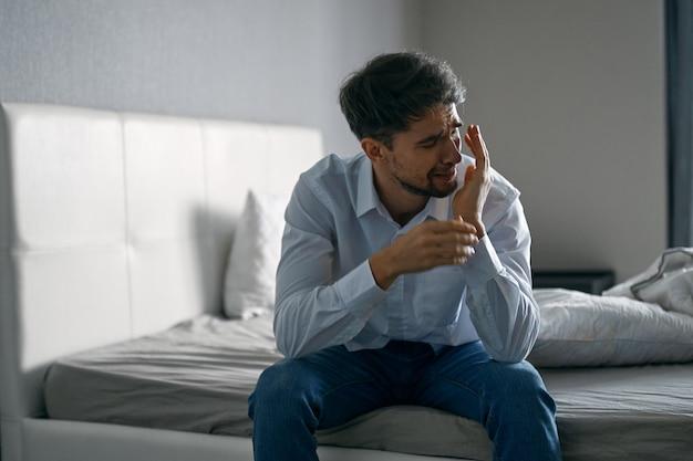 우울한 침대에 앉아 젊은 남자