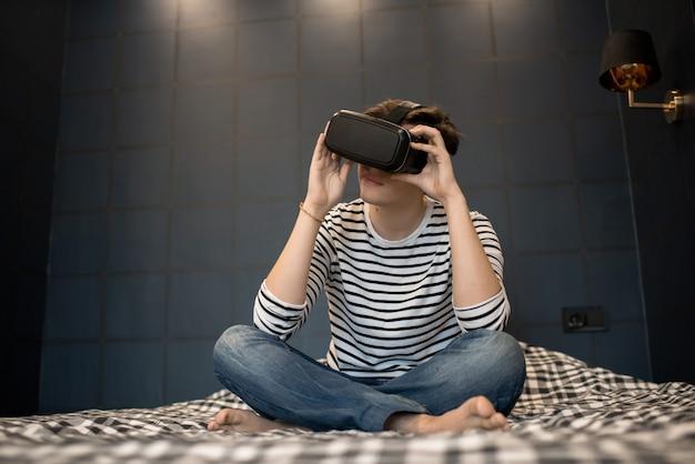 Vr 안경을 사용하여 침대에 앉아 젊은 남자