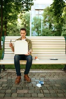 Молодой человек сидит на скамейке среди мусора в парке, занимается волонтерством