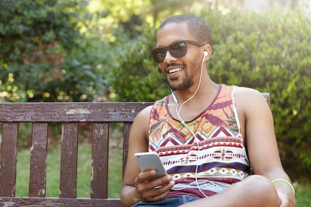 公園のベンチに座って音楽を聴いている若い男
