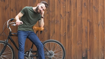 Young man sitting on bicycle against wooden background
