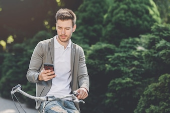 Young man sitting on bicycle looking at smartphone