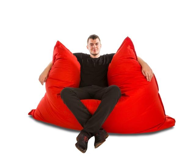 居間または白で隔離された他の部屋のための大きな赤いお手玉ソファの椅子に座っている若い男