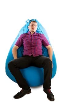 白で隔離の青いお手玉に座っている若い男