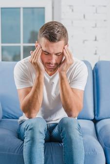 Молодой человек сидит на синем диване, чувствуя сильную головную боль, касаясь его лба