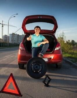 Молодой человек сидит на багажнике автомобиля и держит ногу на запасном колесе