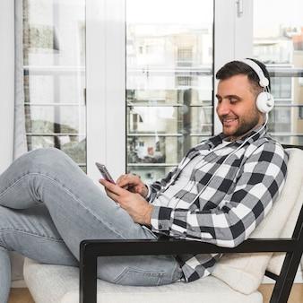 Молодой человек сидит на стуле, слушая музыку на наушники через мобильный телефон