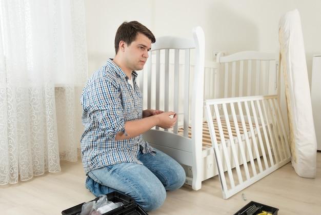 Молодой человек сидит на полу и ремонтирует детскую кровать в детской