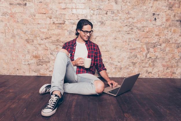Молодой человек сидит на полу с ноутбуком и пьет кофе