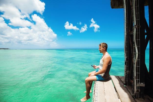 トロピカルビューの写真を撮る桟橋に座っている若い男