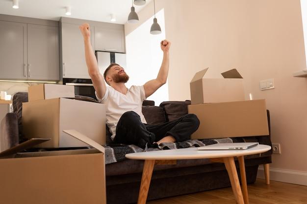 Молодой человек сидит на диване и радуется дома. улыбающийся европейский парень. портативный компьютер на столе. картонные коробки с вещами. концепция переезда в новую квартиру. интерьер однокомнатной квартиры